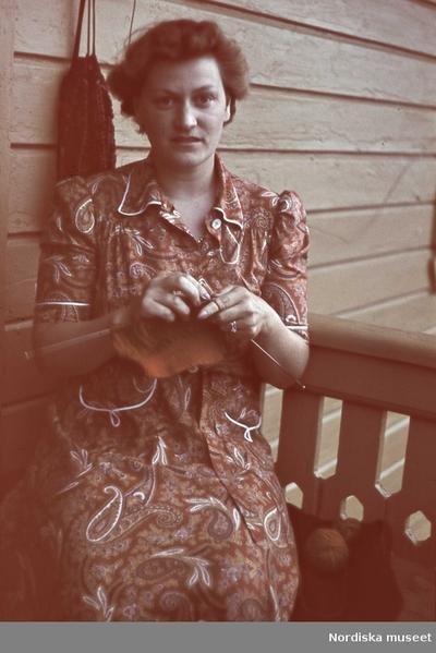 Kvinna i paisleymönstrad klänning sitter på en veranda och stickar.