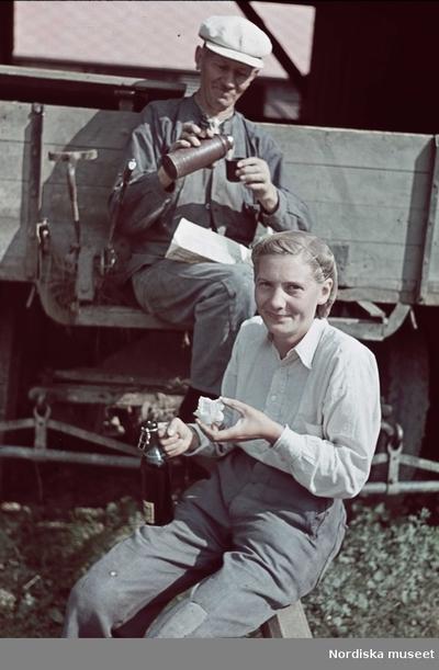 En kvinna i hårnät och en man i keps tar matrast. Kvinnan äter en smörgås, mannen häller upp kaffe i locket till en termos.