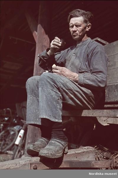 En man tar matrast. Han dricker kaffe ut locket till en termos och håller en smörgås i handen.