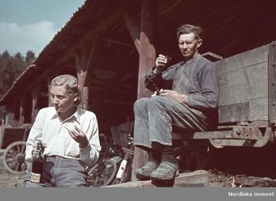 En kvinna i hårnät och en man i keps tar matrast. Kvinnan äter en smörgås, mannen dricker kaffe ur locket till en termos.