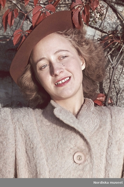 Kvinna i grå kappa och brun hatt.