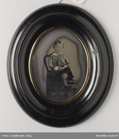 Barn Kläder : Barnkläder Kläder : Skor Motivkategori : Föremål Motivkategori : Porträtt Pojke Tidsanda : 1800-tal