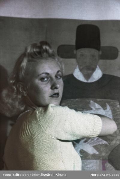 Porträtt av okänd kvinna framför målning.