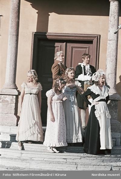 Skådespelare iklädda 1800-talskläder på trappan till Skogaholms herrgård, Skansen.