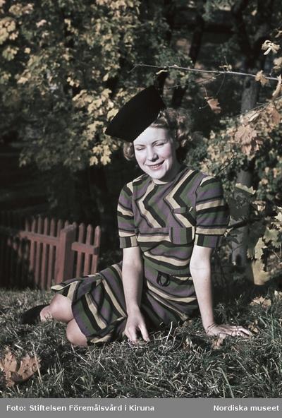 Kvinna i randig klänning och svart hatt.