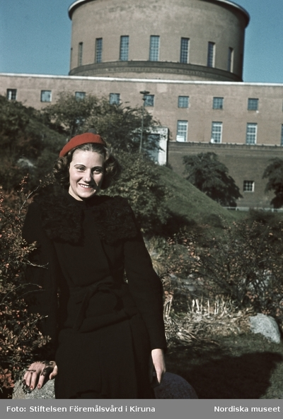 Kvinna iklädd svart dräkt och röd basker. Stockholms stadsbibiliotek i bakgrunden.