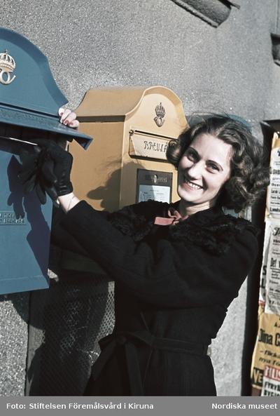 En kvinna lägger ett brev i en blå postlåda.