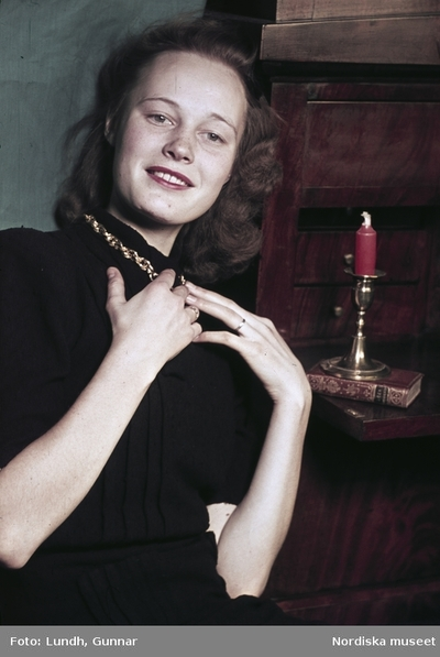 086f20ef4974 Kvinna i svart skjorta med guldlänk runt halsen. Mässingsljusstake.