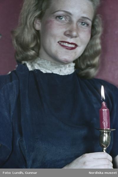Kvinna med brinnande rött stearinljus i mässingsljusstake