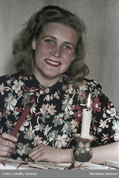 Kvinna i blommönstrad blus med lackstång, julklappspaket och brinnande stearinljus