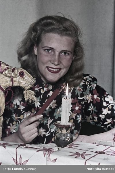 Kvinna i blommönstrad blus med lackstång, julbock, julklappspaket och brinnande stearinljus