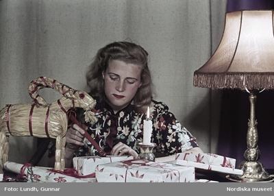 Kvinna i blommönstrad blus lackar julklappspaket. Julbock, lampa och brinnande stearinljus på bordet.