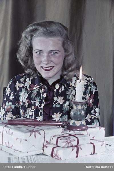 Kvinna i blommönstrad blus sittandes vid bord med lackstång, julklappspaket och brinnande stearinljus