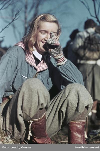 Flicka klädd i friluftskläder. Jacka, byxor, läderstövlar och stickade vantar.