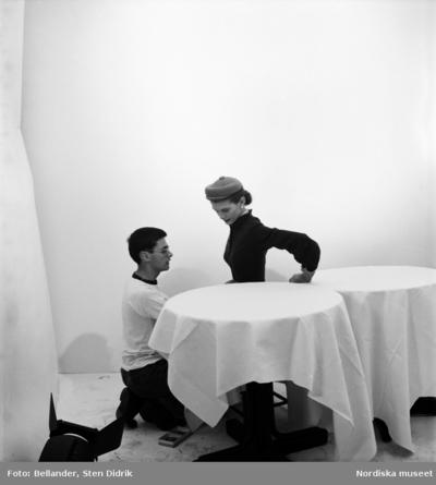 Fotografen Richard Avedon rättar till klädseln på en kvinnlig modell. Fotostudio.