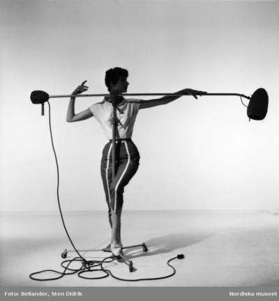 Modebild. Kvinnlig modell poserar vid en studioblixt.