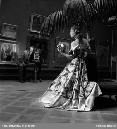 En kvinnlig modell poserar vid en palm i en utställningssal medan Rolf Winquist fotograferar.