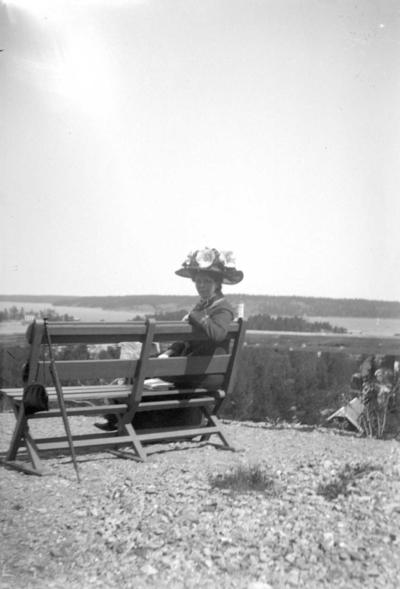 En kvinna med stor hatt med blommor sittande på en bänk.