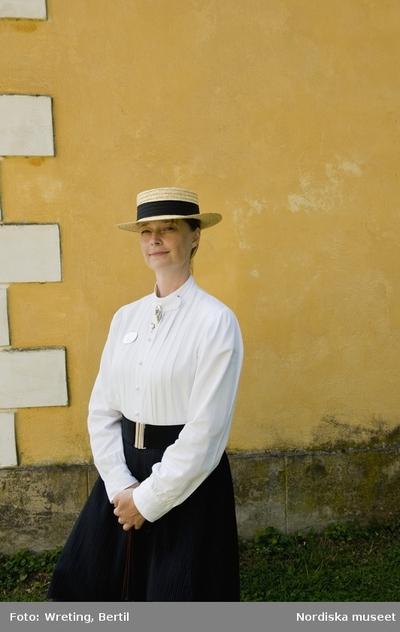 d21e3640a5d5 Guiden Maria iklädd halmhatt, vit skjorta och svart kjol