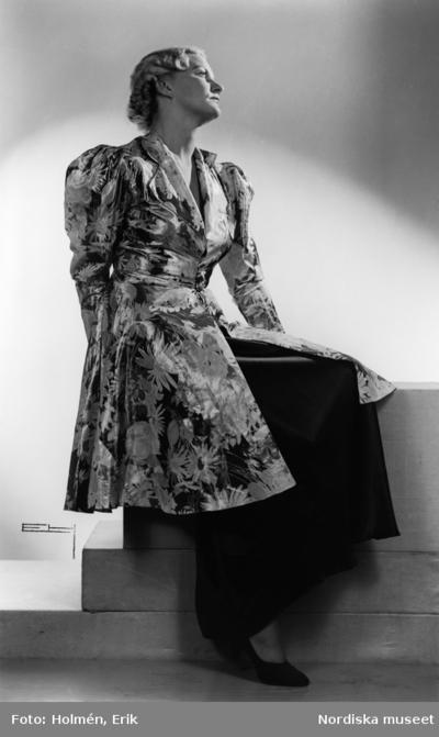 Modell i storblommig klänning med pösärm, svart kjol under och svarta pumps, sitter på en trappa.