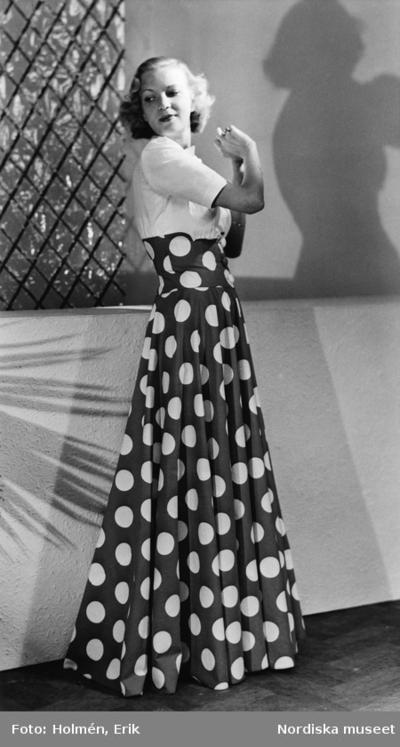 aad39e252f30 Modell i hellång klänning med vit överdel och prickig kjol. Rutigt galler i  bakgrunden och