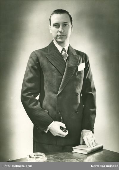 444e3a7725a3 Porträtt av en man i kostym och pipa i handen.
