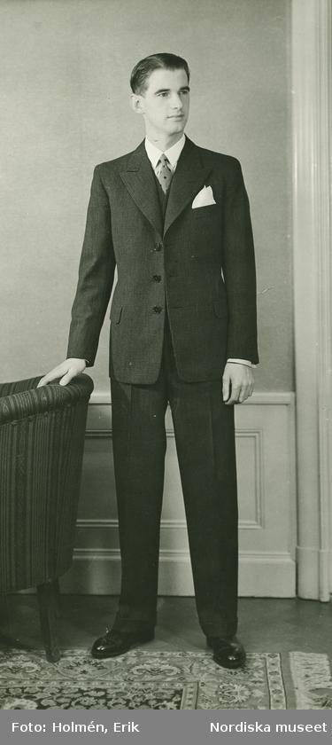 dbcd9ecb8b27 Helporträtt av en man i kostym i interiör.