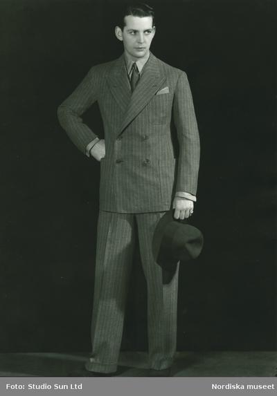 f8ab55306c9a Helporträtt av en man i kritstrecksrandig kostym och Fedorahatt i handen.