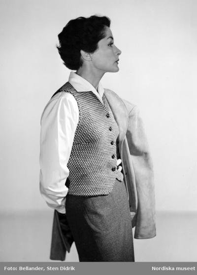 Modell klädd i kjol, blus och väst, håller jacka i handen.