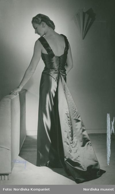 Modell i buteljgrön aftonklänning i blank helsilke med pärlbroderier på axelbanden, från Molyneux.