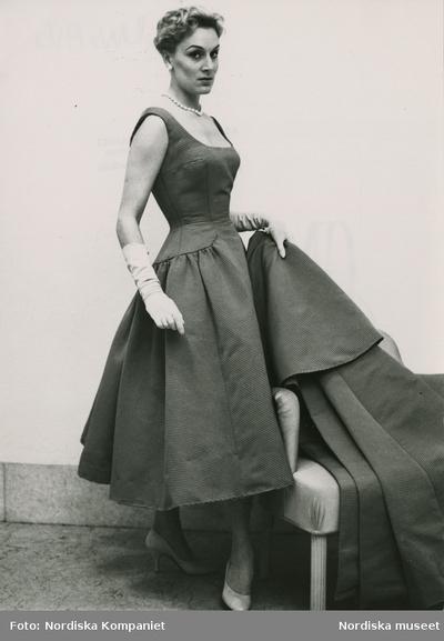 Modell i klänning med uställd kjol, handskar, pälshalsband, örhänge och pumps, håller i tygstycke i samma material som klänningen.