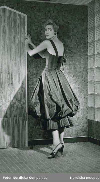 Modell i klänning med plisséer och rosett, örhänge och högklackade skor, vid kaklad vägg.