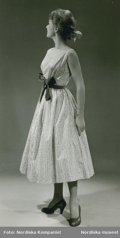 300012f61f6d Modell i klänning med linjeprickar och rosett, handskar och band i