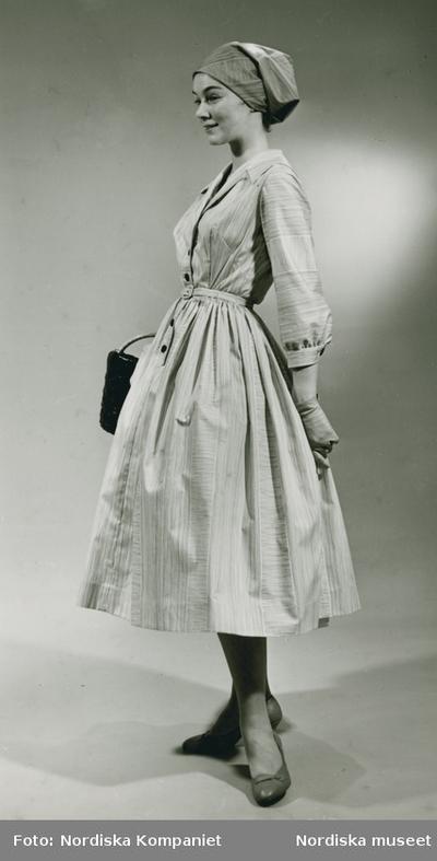 c08edf9efc3a Modell i klänning och sjalett., väska och handskar.