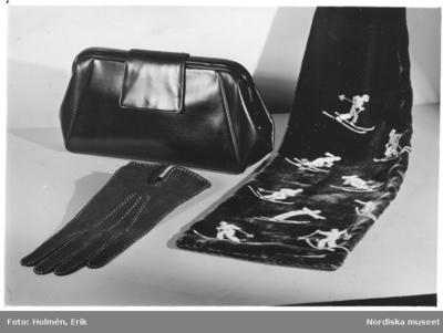Väska i kalvskinn med galalitbåge, sammetsscarf med motiv av skidåkare, handskar av den korta handskmodellen med stickning.