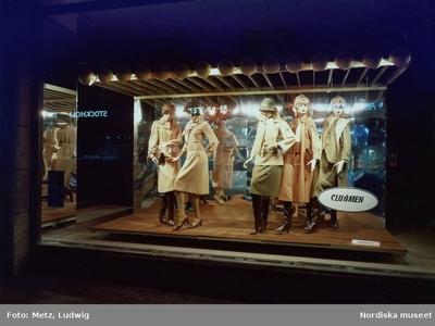 61bbc741d00 Skyltfönster på Nordiska Kompaniet. Skyltdockor i kappor, kjolar, hatt och  stövlar i beiga och bruna nyanser från Clubmen.
