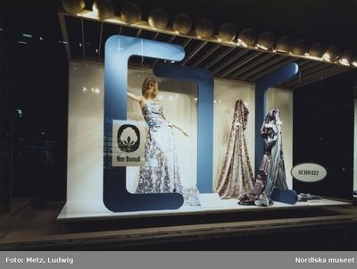 Skyltfönster på Nordiska Kompaniet. Mönstrade tyger och skyltdocka i klänning i mönstrat tyg. Schweiz-skylt.