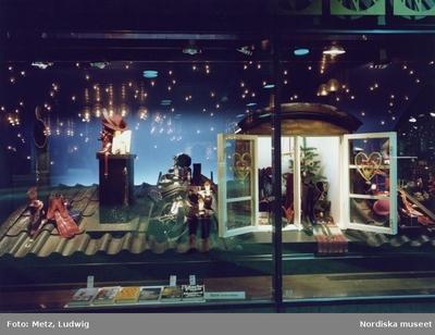 8a72eba1982 Skyltfönster på Nordiska Kompaniet. Julskyltning. Stövlar, skor, hattar och  juldekorationer på ett