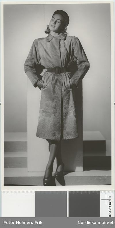 Nordiska Kompaniet. Kvinna i ljus päls och svart skärp. Text på baksidan  e1a898f7350ab