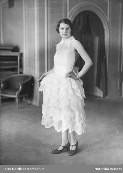 Modell i vit klänning med bladformade etapper och spetsig krage, skor med t-slejf.