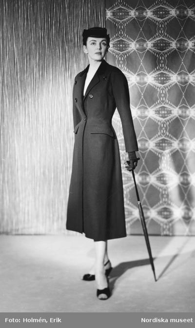 Modell i kappa, hatt och paraply. Från Madeleine de Rauch.