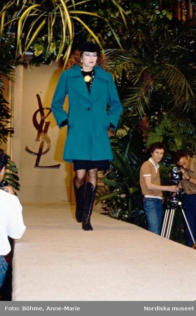Modevisning. Modell i turkos kappa, svart hatt och stövlar. Yves Saint Laurent.