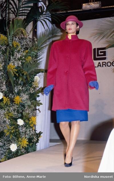 Modevisning. Modell i cerise kappa, hatt, blå kjol och handskar. Från Laroche.
