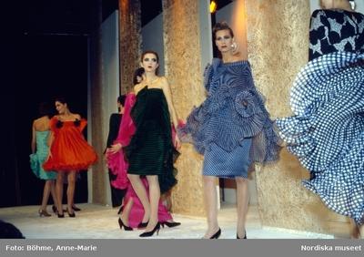 Modevisning. Modeller i mönstrade och enfärgade klänningar i olika längder och former. Från Cardin.