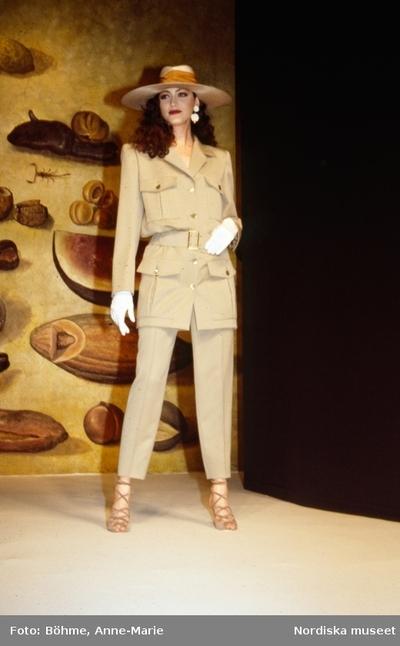 Modevisning. Modell i beige jacka och byxor med pressveck. Sandaletter, handskar och hatt. Från Laroche.