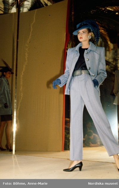 Modevisning. Modell i grå jacka och byxor, blå hatt och handskar, samt örhängen. Från Givenchy.