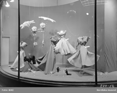 c140f35ddac Skyltfönster på Nordiska Kompaniet. Aftonklänningar, accessoarer och  martiniglas.