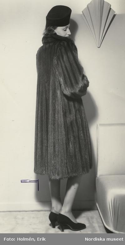 Nordiska Kompaniet. Kvinna i mörk päls och hatt. text på baksidan  425d16cc8fdd6