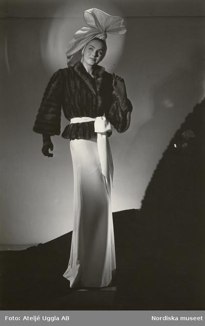 Nordiska Kompaniet. Kvinna i ljus aftonklänning och höftlång pälsjacka.  Ljust skärp av tyg. 72bb6c8869d3d