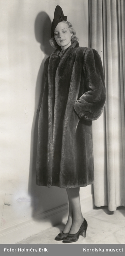 Nordiska Kompaniet. Kvinna i mörk päls och hatt. ec157ee1730a7